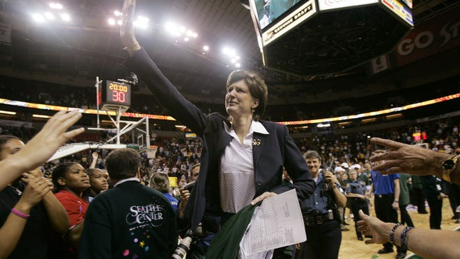 Coach Anne Donovan waves to fans as she leaves the court after a victory against the Connecticut Sun in 2004 gave the Seattle Storm the WNBA championship.