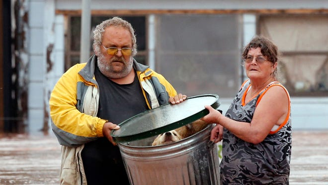George and Susan Kruger make one of three trips with their animals from their flooded house to safety on Sunday, May 24, 2015 in Purcell, Okla. Rising water from overnight rains began to rise early in the morning.  The Krugers refused to leave their home and made several trips to retrieve five dogs and a baby chick.