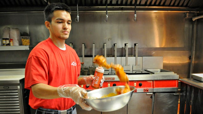 Kori Quillo coats a fresh batch of chicken wings in Buffalo bleu sauce at Lily's Wings in its new location on Northway Drive on Oct. 8.