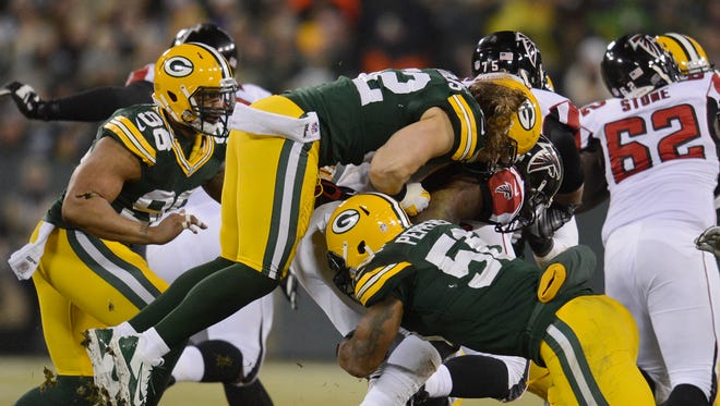 Green Bay Packers linebacker Clay Matthews (52) combines with Julius Peppers (56) for a tackle against the Atlanta Falcons during Monday night's game at Lambeau Field.  Evan Siegle/P-G Media