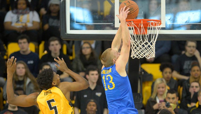 Delaware's Kyle Anderson (13) dunks while Towson's Walter Foster trails Saturday in Towson, Md.