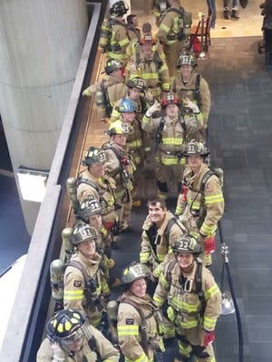 The Brighton Area Fire Department's team lines up for their turn to climb 71 flights of stairs during the American Lung Association's Fight for Air Climb on Sunday in Detroit.