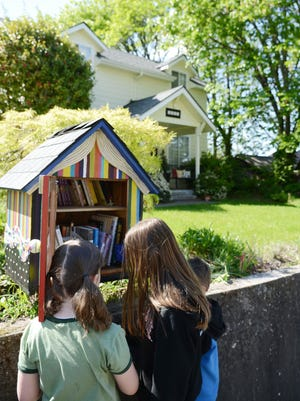 Bella Ramey (left), Rae Millis and Will Ramey look for books at a Free Little Library in a neighborhood near South Salem High School. The little library is open for anyone to take a book and leave a book.