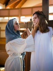 """Mary, the Mother of Jesus, played by Ellie Staehling, tries to comfort Jesus, played by Tess Huhn in Shepherd of the Hills Catholic School's dramatization of """"The Living Way of the Cross."""""""