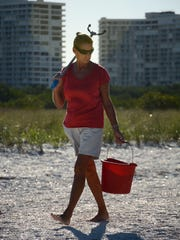 Beach cleanup veteran Katie O'Hara walks the water's edge in this file photo.