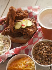 A basket of hot breast and wings with sides of pimento mac and cheese, cole slaw and a black-eye pea salad at Hattie B's.