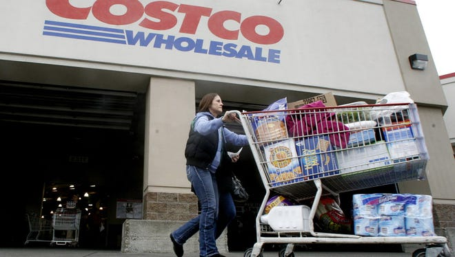 A shopper leaves a Costco store in Portland, Ore. Costco shoppers who have been limited for years to American Express credit cards may be able to pluck a new option from their wallets or purses next year when an exclusivity deal between the two companies expires on March 31, 2016.