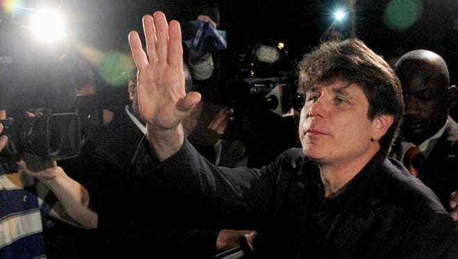 In this March 15, 2012 file photo, former Illinois Gov. Rod Blagojevich waves as he departs his Chicago home for Littleton, Colo., to begin his 14-year prison sentence on corruption charges. On Tuesday, Aug. 4, 2015, lawyers for Blagojevich filed a request with the 7th U.S. Circuit Court of Appeals in Chicago to rehear his appeal after three judges recently overturned five of his 18 corruption convictions. Blagojevich is hoping the full court will overturn more counts. Full-court hearings aren't granted automatically.