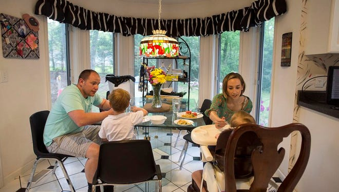 """Mara Watts feeds her 19-month-old daughter Henley while her husband Adam and four-year-old son eat a dinner of chicken pot pie and watermelon May 2, 2016.  Adam supported her during her time with PPD, but they often got in to arguments using phrases like """"you're not the mom, you don't understand."""""""