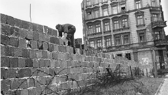 An East Berlin policeman puts bricks in place as the Berlin Wall, separating East and West Berlin, Germany, is raised to 15 feet on Sept. 9, 1961.