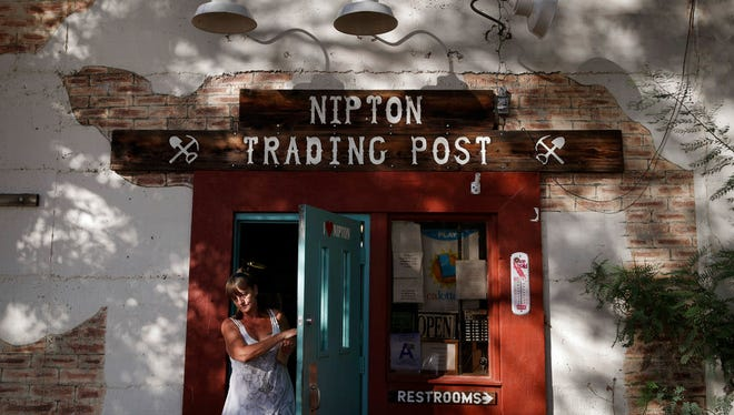In this Aug. 3, 2017, file photo, a woman leaves the Nipton Trading Post in Nipton, Calif. A Phoenix-based marijuana technology company bought the town of Nipton for $5 million with ambitious plans to turn its dusty, nearly deserted 80 acres into a pot-friendly resort destination just an hour outside Las Vegas. But the company announced earlier in March 2018 it has sold Nipton to Delta International Oil & Gas in a cash and stock deal worth about $7.7 million.