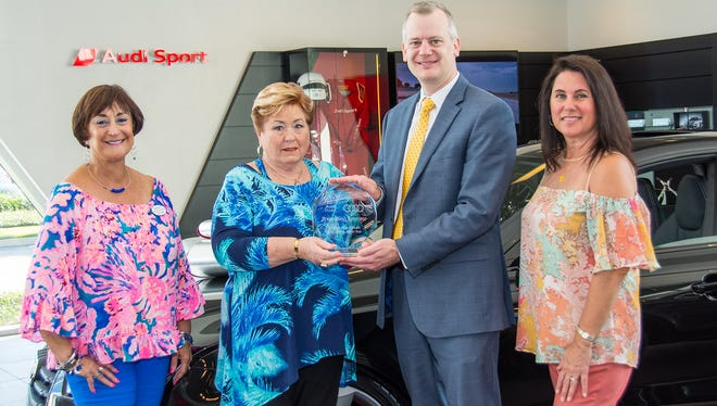 Audi Stuart General Manager Devin Carlson, second from right, receives a plaque from Woman's Club of Stuart members Janie Copes, left, Polly Pharo and Lisa Pinkley thanking the dealership for its continued support of the club's annual Holiday Home Tour.