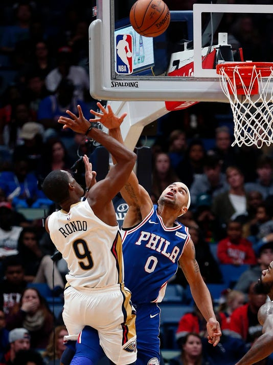 Philadelphia 76ers guard Jerryd Bayless (0) goes up against New Orleans Pelicans guard Rajon Rondo (9) in the second half of an NBA basketball game in New Orleans, Sunday, Dec. 10, 2017. (AP Photo/Gerald Herbert)