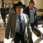 Former New Mexico state Sen. Phil Griego, left, and his attorney Tom Clark, center, walk out of an arraignment in Santa Fe District Court in Santa Fe, N.M., Monday, April 4, 2016. The Democrat from San Jose was released pending trial after pleading not guilty to fraud and bribery charges stemming from his role in the sale of a state-owned building in Santa Fe.