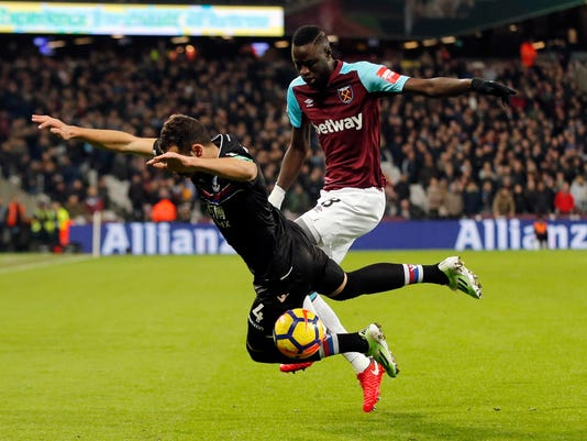 Crystal Palace's Luka Mlivojevic, left falls as he vies for the ball with West Ham United's Cheikhou Kouyate during their English Premier League soccer match between West Ham United and Crystal Palace at the London stadium in London, Tuesday, Jan. 30, 2018. (AP Photo/Alastair Grant)