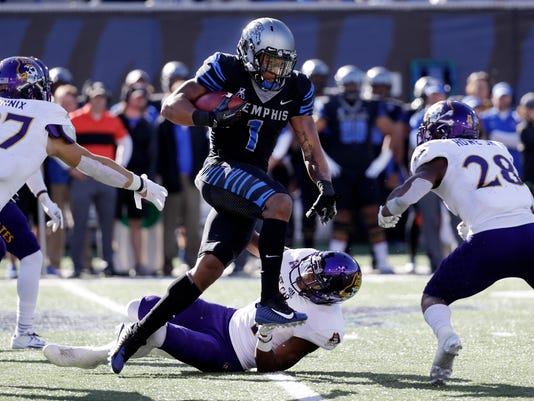 Memphis kick returner Tony Pollard (1) gets past East Carolina's Darius Pinnix (27) and Hussein Howe (28) as Pollard runs back a kickoff 100 yards for a touchdown in the second half of an NCAA college football game, Saturday, Nov. 25, 2017, in Memphis, Tenn. Memphis won 70-13. (AP Photo/Mark Humphrey)