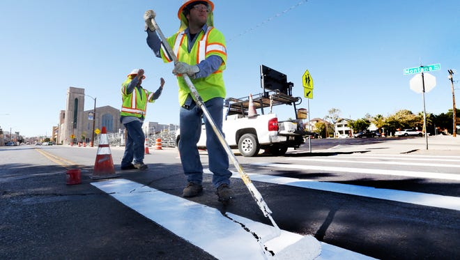 Esteban Zavala, foreground, and Carpio Enrique of the city Street & Maintenance Department paint crosswalk striping on Montana Ave. at Ange near the reviewing stands Wednesday in anticipation of Thursday's 80th FirstLight Federal Credit Union Sun Bowl Parade.