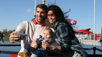 23-time Olympic gold medalist Michael Phelps and wife Nicole Johnson pose for a selfie with their son Boomer next to a giant version of the Ryder Cup trophy at Hazeltine National Golf Club.