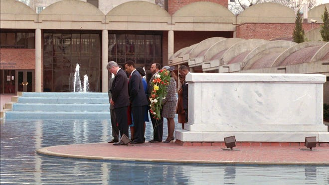 President Clinton bows in prayer after placing a wreath in front of Martin Luther King's crypt in Atlanta on Jan. 15, 1996. King's son, Dexter Scott King is immediately behind the president.