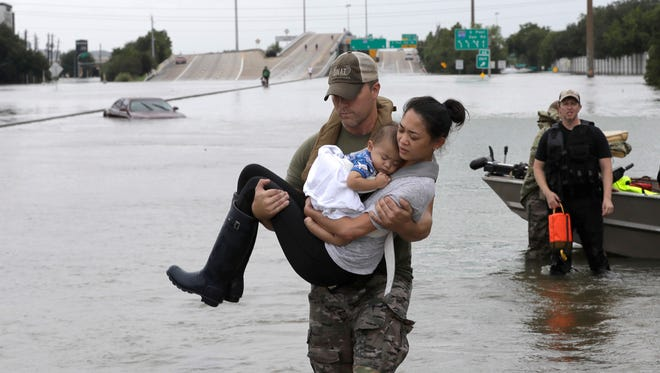 Houston Police SWAT officer Daryl Hudeck carries Catherine Pham and her 13-month-old son Aiden after rescuing them from their home surrounded by floodwaters from Tropical Storm Harvey on Aug. 27, 2017, in Houston. The remnants of Hurricane Harvey sent devastating floods pouring into Houston Sunday as rising water chased thousands of people to rooftops or higher ground.