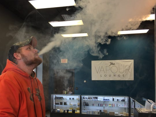 CJ Apfelbeck, 24, of Schofield, is shown vaping on Friday at The Vapour Lounge on Rib Mountain Drive. The new vape shop opened its doors this week.