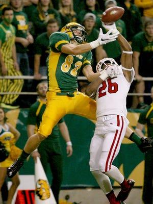 North Dakota State receiver Zach Vraa (82) battles South Dakota defensive back Chris Tyler (26) on a first-quarter pass play during an NCAA college football game Saturday  in Fargo.