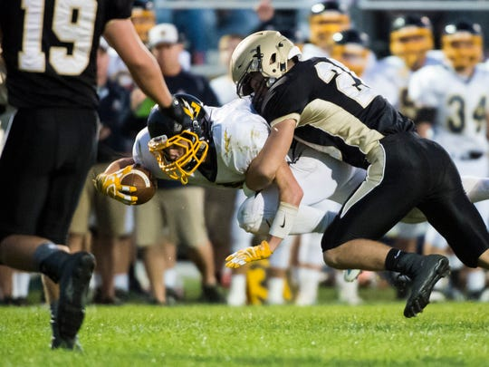 Littlestown's Corbin Brown is tackled by Delone Catholic's Tyler Monto Friday, Sept. 29, 2017. The Bolts defeated the Squires 28-27.