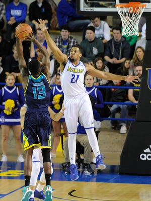 Delaware's Marvin King-Davis (21) jumps up to block a shot attempt from UNCW's Chuck Ogbodo (13).