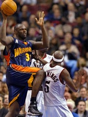 Golden State Warriors' Adonal Foyle, left, passes the ball above Philadelphia 76ers' Vonteego Cummings, right, and Jabari Smith, background, during a Feb. 20, 2002 game in Philadelphia.