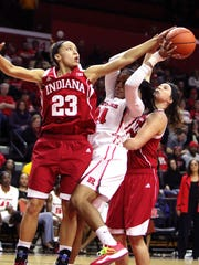 Rutgers forward Betnijah Laney grabs a rebound between two Indiana players.
