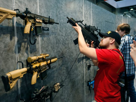 Nolan Hammer looks at a gun at the Heckler & Koch booth at the Shooting, Hunting and Outdoor Trade Show, Tuesday, Jan. 19, 2016, in Las Vegas.