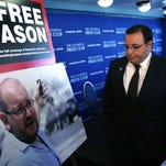 A file picture taken on September 10, 2013 shows Iranian-American Washington Post correspondent Jason Rezaian posing for a photo while covering a press conference at Iran's Foreign Ministry in Tehran.  The trial of Jason Rezaian resumed on August 10, 2015 in Tehran, in what could be the final hearing before a judgment is issued on whether he spied on Iran.  AFP