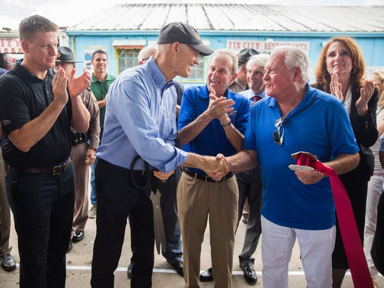Gov. Rick Scott shakes hands with Bert Pohlmann, owner of Tin City, which officially reopened during a ribbon-cutting Monday, Oct. 9, 2017, after damage from Hurricane Irma halted business.