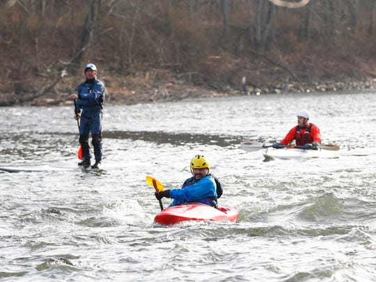 Adam Holton paddles his kayak into a stationary wave on the Chenango River as, from left, Steve Busch and Glenn Miga observe in Chenango Forks on Monday, December 4, 2017.