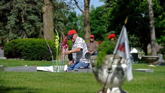 Jim Ptak puts flowers on his grandparents' headstones while his brother, Rich, watches Friday at Woodlawn Cemetery in Sioux Falls.
