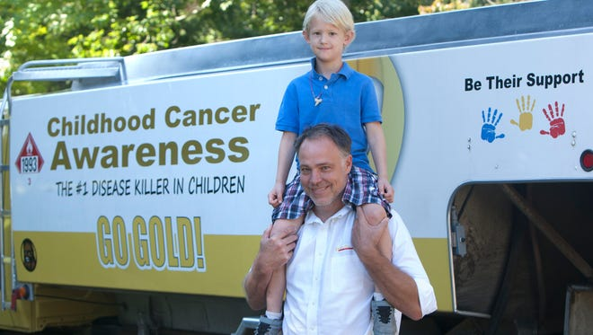 Caeden Stoll (right), 5, Toms River, is a cancer survivor. He is with Casey Boynton, general manager of Dover Oil. The company repainted its delivery truck with a childhood cancer awareness message.
