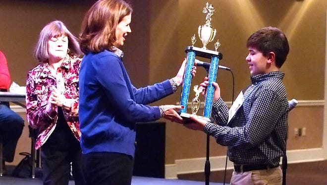 Hayden McCuan, a sixth-grader at Trinity Christian Academy, receives the first-place trophy for the 2014 West Tennessee Regional Spelling Bee  in this March 2014 file photo.