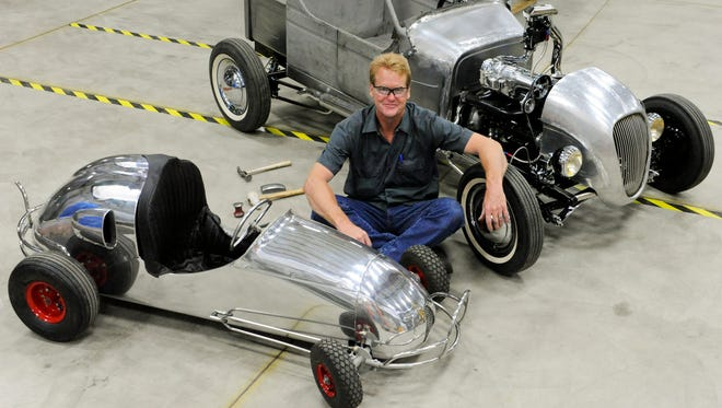 Metal shaping artist Dave Byron poses with the race car that he made of a 1950's reproduction of a quarter midget race car, foreground, and a custom 1950's hot rod car that he is restoring and fabricating for a client at Baileigh Industrial in Manitowoc.