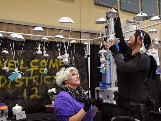 Gina Schmidt, left, and Kimberly Rorabaw of Homewood Suites decorate their Business Expo booth in a Hunger Games theme Thursday afternoon. The event is sponsored by the Wichita Falls Chamber of Commerce.