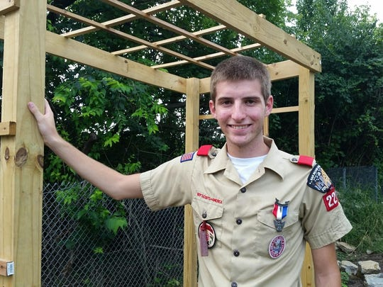 Abe Wickstrom stands next to a grapevine trellis constructed for his Eagle Scout project.