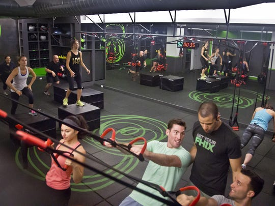 """Gym instructor Javier """"Coach Java"""" Martinez, second from right, guides participants doing inverted rows on a jungle gym at the Fhitting Room boutique fitness studio."""