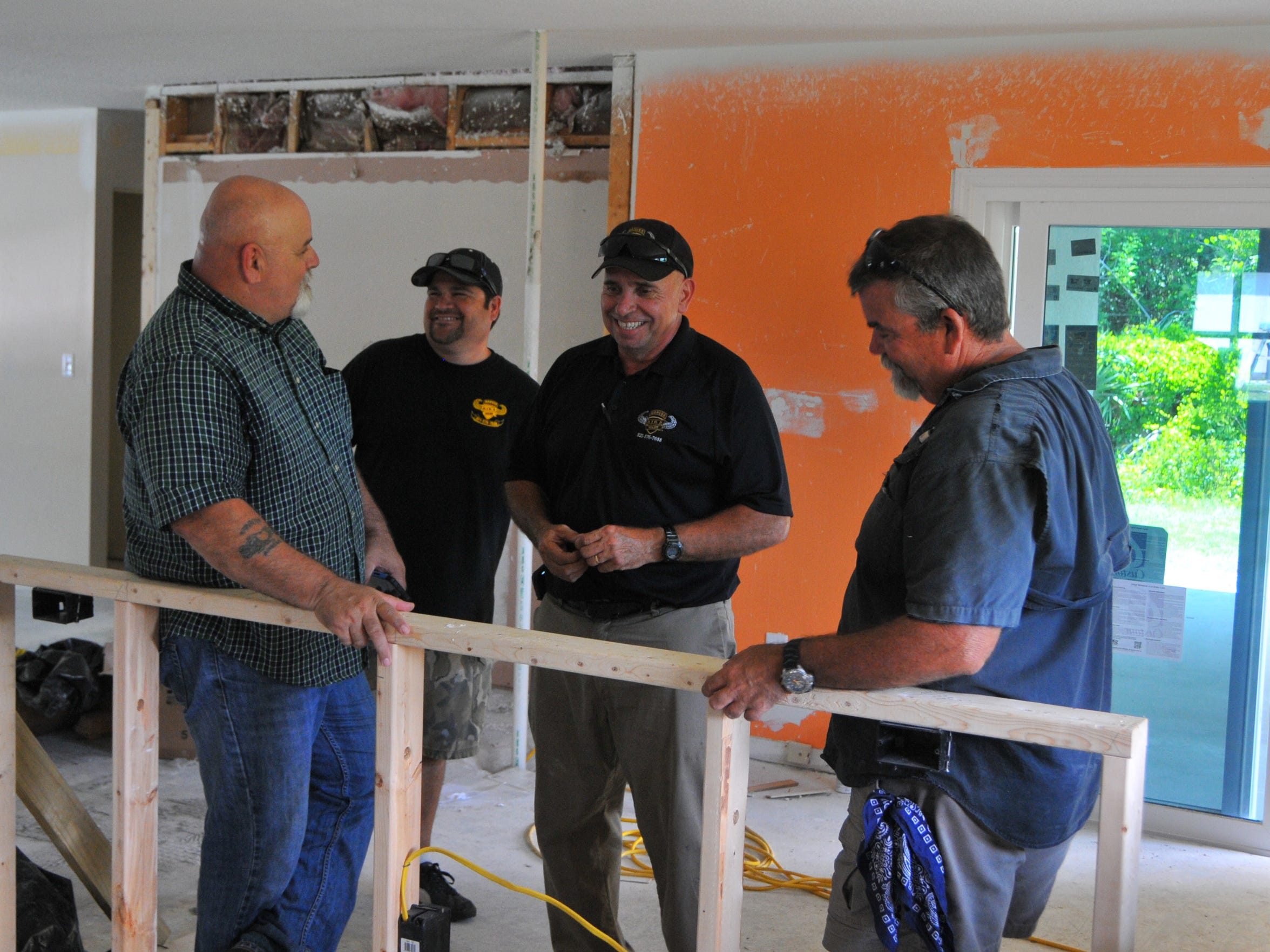 David Isnardi, with the Space Coast Paratroopers Association, talks with Marc Marttinez and Jerry Lawson with Ranger Air and Heat, and Bob Williams with the city of Palm Bay at house being refurbished for a wounded veteran.