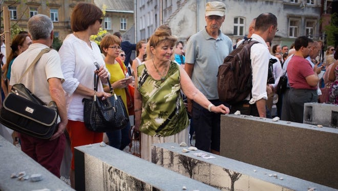 Visitors to the new Space of Synagogues memorial place stones in remembrance of the dead in Lviv, Ukraine on Sept. 4, 2016.