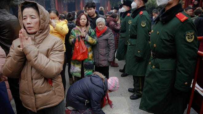 Women pray in front of paramilitary policemen at Yonghegong Lama Temple on the first day of the Lunar New Year of the Rooster in Beijing.