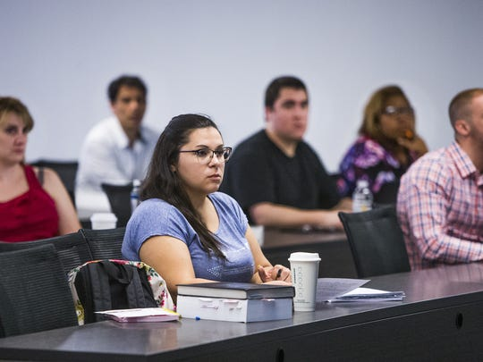 Rebecca Plascencia, 25, Phoenix, middle, listens during