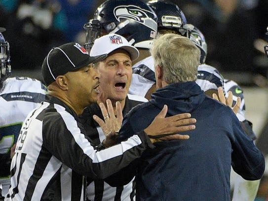 Seattle Seahawks head coach Pete Carroll is held back