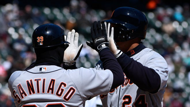 Tigers first baseman Miguel Cabrera (24) high-fives first base coach Ramon Santiago (39) after he hit a two-RBI single against the White Sox in the third inning on Saturday, April 7, 2018, in Chicago.