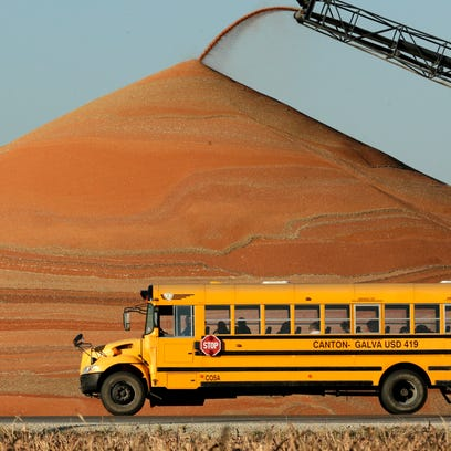 A school bus passes a pile of milo at a grain storage