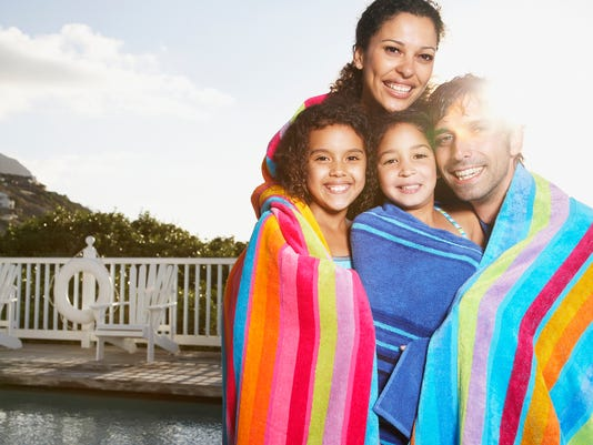 Man and woman with girls in beach towels by pool outdoors