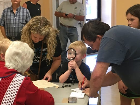 Young Sawyer Scism plays with a magnifying glass as his mother, Jamie Scism, fills out paperwork to vote at Tennessee Ridge City Hall on Aug. 2.